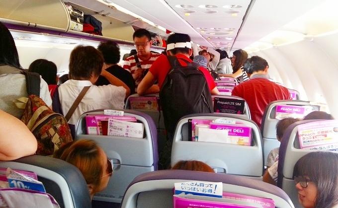 香港国際空港でピーチアビエーションの旅客機から降りる準備をする乗客たち