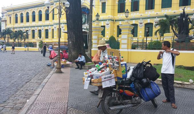 ベトナム・ホーチミン市1区 ドンコイ通り バイクの後ろにドリンクや煙草を乗せて売っている物売り