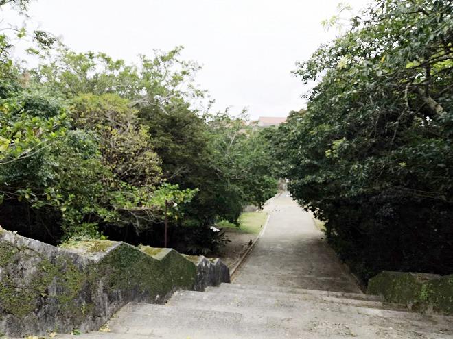 那覇 首里城 園比屋武御嶽石門とアカギの大木の間の森の中に下る階段