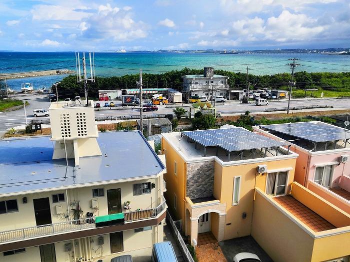 沖縄県金武町屋嘉「スノーボールコンドミニアム」黄色のミセス スノーボール棟の屋上からの屋嘉の住宅街と金武湾の眺め